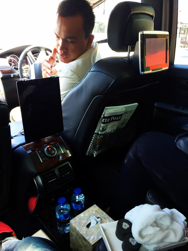 Diwa, our St Regis Bali Nusa Dua driver explaining the various screens and snacks he has brought along with him for the journey from the Le Meridien Bali Jimbaran